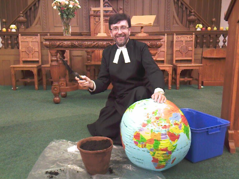 Minister with trowel, pot and globe